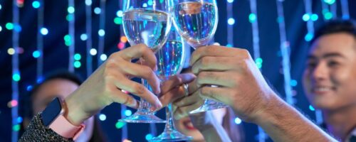 Hands of people toasting with glasses of wine in night club at party
